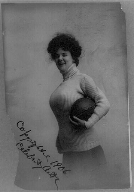 Buxom woman holding football