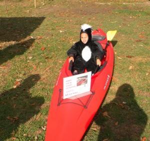 boy in skunk costume riding kayak