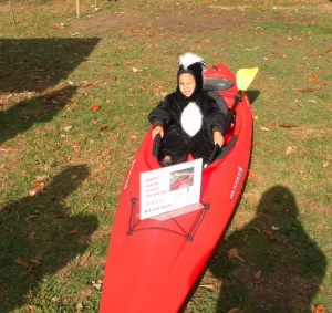 boy in skunk costume riding kayak