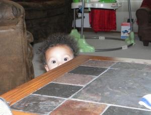 boy peering over tabletop