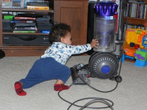 boy reaching out toward vacuum