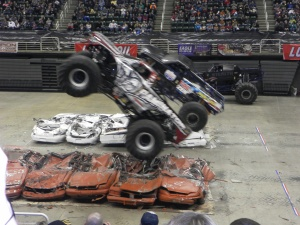 two moster trucks crushing cars